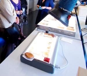 Photographie en couleur de tables lumineuses sur une table. Des négatifs de nitrate sont disposés sur les tables lumineuses. À l'arrière-plan : trois personnes se tiennent près de la table.