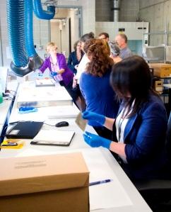 Photographie en couleur d'employés travaillant à un poste de travail où des négatifs de nitrate sont traités. À l'avant plan : une employée manipule un négatif de nitrate; à l'arrière plan : des personnes discutent de l'état ou du traitement d'un autre négatif de nitrate.