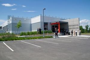 Photographie en couleur d'un immeuble. À l'avant-plan : stationnement; à l'arrière-plan : entrée principale de l'immeuble.