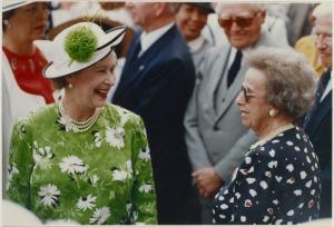 Une photographie en couleur de la Reine Elizabeth II, souriante, dans une foule.