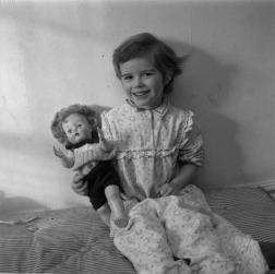Photographie d'une jeune fille assise sur un matelas, une poupée dans le bras.