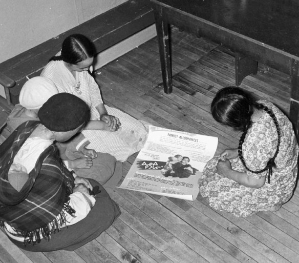 Des femmes examinent une affiche sur les allocations familiales à Baker Lake (Qamanittuaq), au Nunavut. Photo prise par un photographe inconnu, Santé et Bien-être social Canada (MIKAN 3613868)