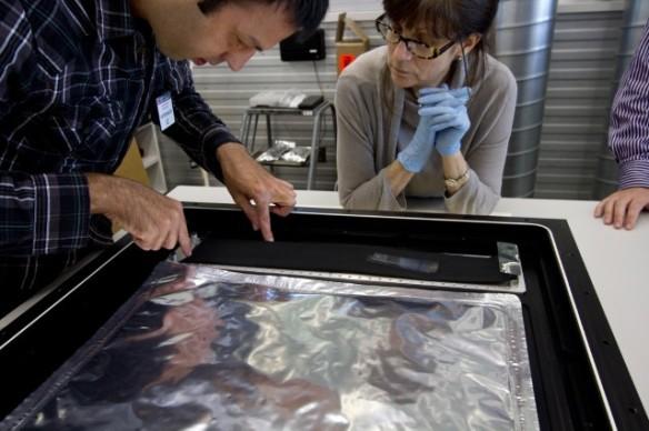 Des restaurateurs posent à l'intérieur du boîtier un tissu de carbone activé qui permet de filtrer l'air, absorbant ainsi les polluants atmosphériques.