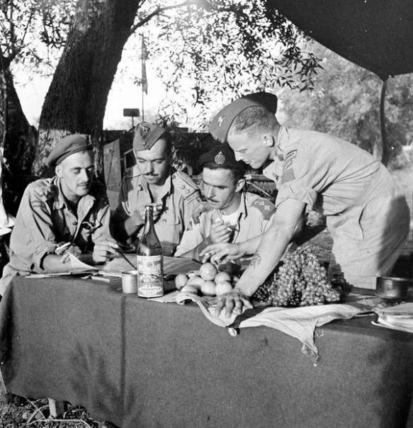 Photographie noir et blanc de quatre hommes autour d'une table étudiant des documents; trois sont assis et un se tient debout, chacun une cigarette à la main. Une bouteille de vin et plusieurs fruits reposent sur la table.