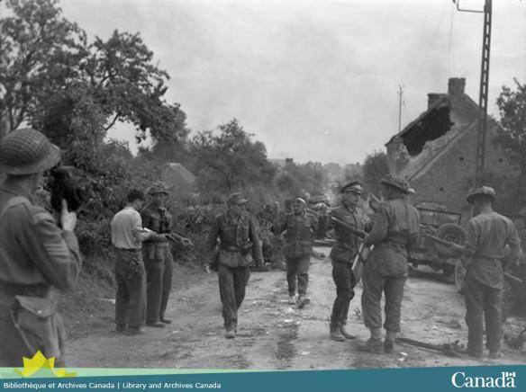 Photo noir et blanc montrant un groupe de soldat allemande avec les mains en l'air et entouré de soldats canadien.