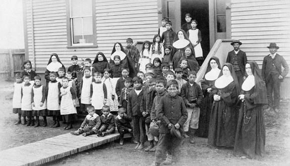 Photographie noir et blanc d'un groupe composé de filles et de garçons autochtones, de sœurs et de deux hommes devant un édifice