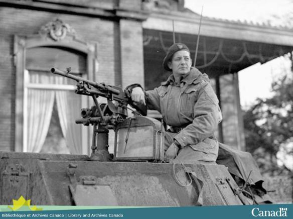 Photo noir et blanc montrant un homme assis sur la tourelle d'un char d'assaut appuyé sur la mitrailleuse et regardant vers la gauche.