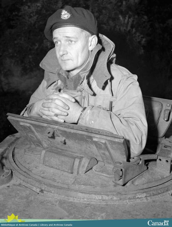 Photo noir et blanc montrant un homme regardant au-dessus de la tourelle d'un char d'assaut.