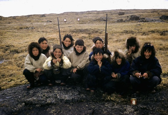 Photo couleur d'un groupe de garçons inuits accroupis sur un rocher plat; deux d'entre eux ont un fusil dans les mains