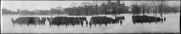Photographie panoramique en noir et blanc présentant quatre groupes de soldats se tenant debout, dehors, en hiver.