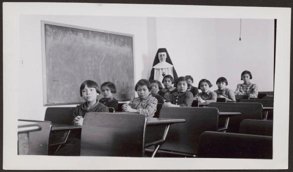 Photographie noir et blanc de filles autochtones assises à leur pupitre; une sœur est debout derrière elles.