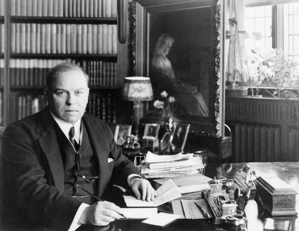 Photo noir et blanc montrant W.L. Mackenzie King assis devant un bureau qui s'apprête à signer des papiers.