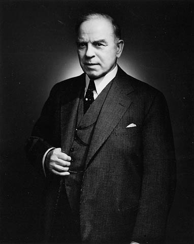 Photo noir et blanc de W.L. Mackenzie King debout tenant sa veste.