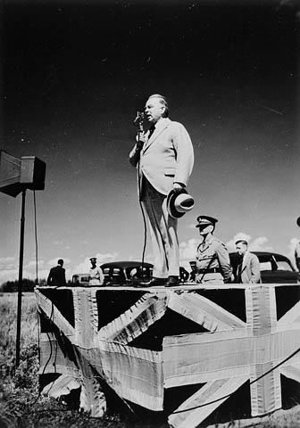 Photo noir et blanc d'un homme debout sur un podium décoré du drapeau de la Grande-Bretagne.