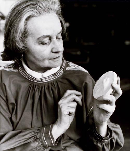 Photo noir et blanc d'une femme observant attentivement le modèle en céramique d'une médaille qu'elle tient dans ses mains.