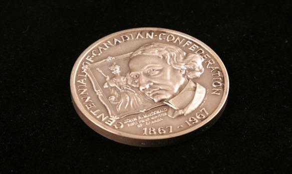 Photographie en couleur montrant une pièce de monnaie avec l'image de John A. Macdonald et un portrait d'une reine dans l'arrière-plan.