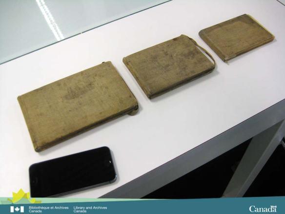 Une photographie en couleur de trois cahiers de dessins tachés déposés sur une table blanche à côté d'un téléphone intelligent afin de comparer la taille des objets.