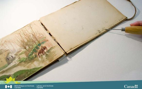 Photo en couleur d'un cahier de dessins ouvert montrant une aquarelle à gauche et la matière transférée à droite.