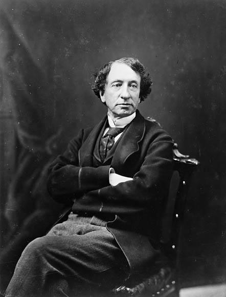 Photographie en noir et blanc de Sir John A. Macdonald assis sur une chaise, avec les jambes et les bras croisés.