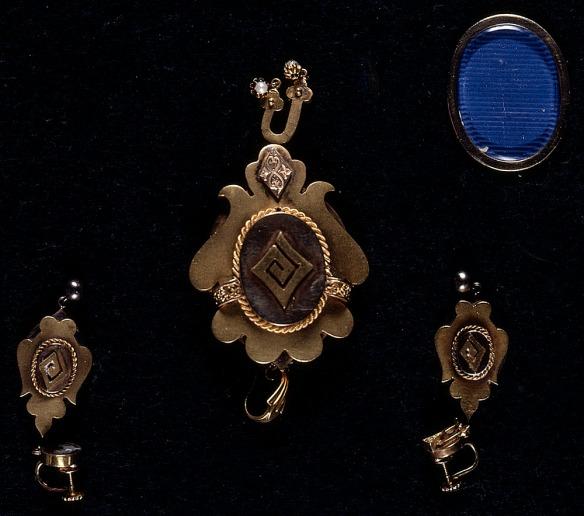 Photographie en couleurs d'un pendentif en or avec un motif stylisé en spirale, et des boucles d'oreilles assorties.