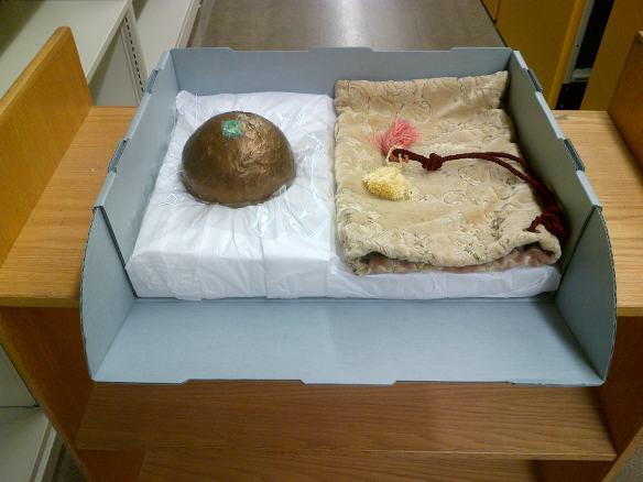 Photographie couleur d'un globe de bronze et du brocart dans lequel il est emballé (à sa droite) dans un contenant matelassé. Une couche de polyester placée sous la pièce métallique recueillera les éventuelles fuites d'eau.