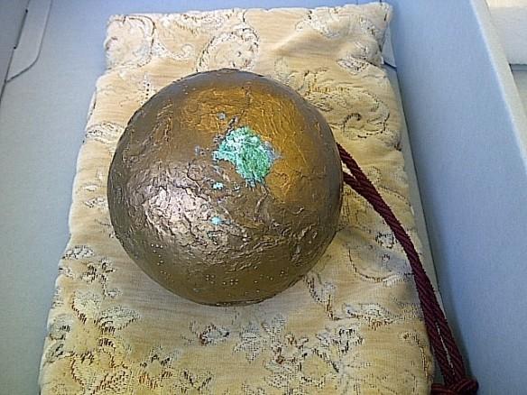 Photographie couleur d'un globe en métal sur un brocart. Une patine de rouille est très visible à la surface du globe.