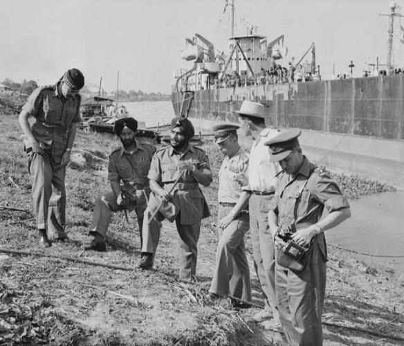 Photo noir et blanc de six hommes debout au bord de la mer; un navire est visible à l'arrière plan.