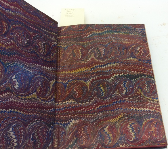 Photographie couleur d'un livre ouvert montrant un somptueux papier marbré servant de page de garde.