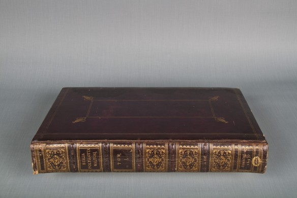 Photographie couleur d'un livre richement décoré à la feuille d'or, portant sur son dos l'inscription Bibla Polyglotta Walton.