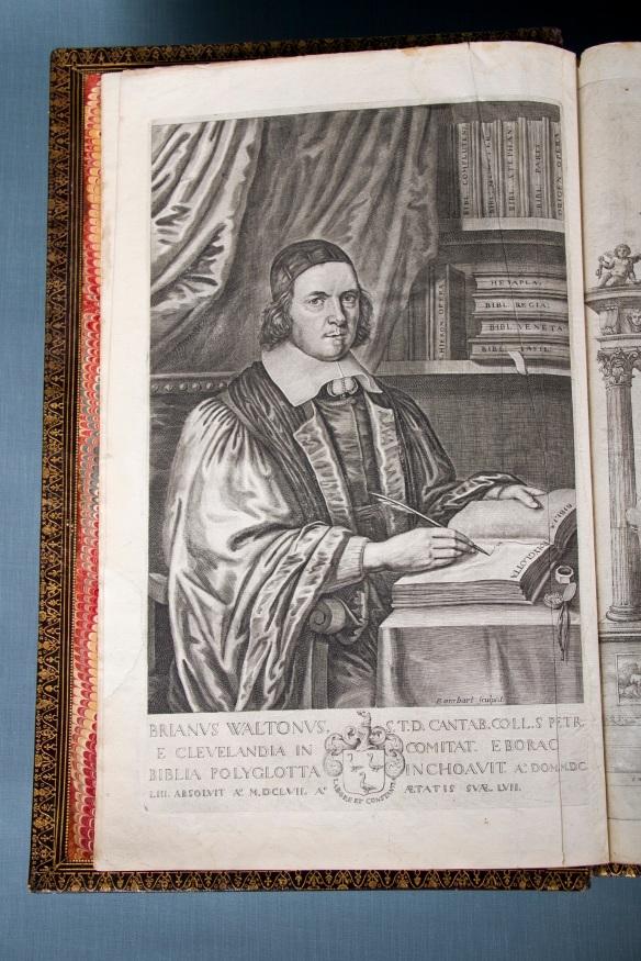 Photographie couleur d'une page avec l'image d'un homme vêtu d'habits épiscopaux, tenant une plume à la main et regardant le lecteur.