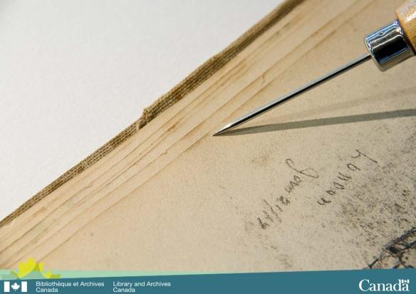 Photographie couleur d'un des côtés d'un livre ouvert montrant des pages ventilées et un outil pointant une tache graisseuse qui se répète sur le bord de chaque page.