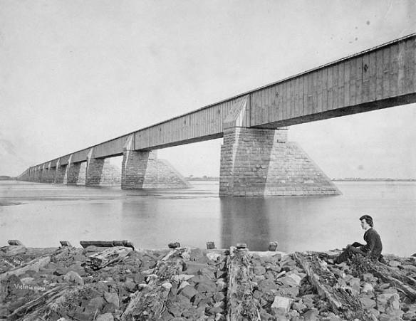 Photographie noir et blanc du pont Victoria de Montréal, avec une jeune femme assise sur un rocher au premier plan.