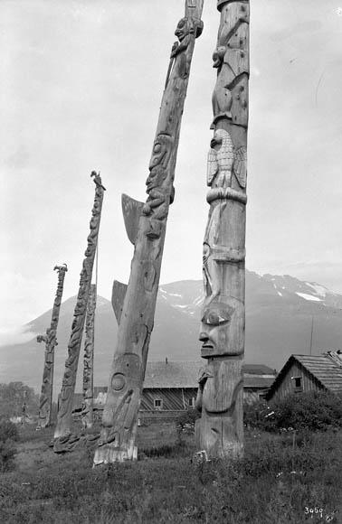 Photographie noir et blanc montrant cinq totems sculptés en bois. En arrière-plan, on voit des maisons et des montagnes.