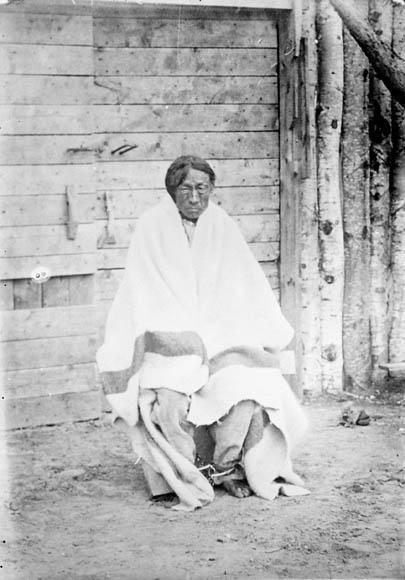 Photographie en noir et blanc d'un homme assis, enveloppé d'une couverture. Il regarde directement le viseur.