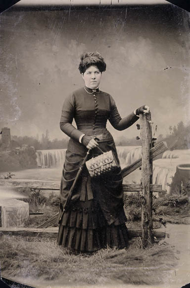 Ferrotype noir et blanc d'une femme posant debout devant une clôture de bois avec derrière elle une toile de fond représentant les chutes du Niagara.