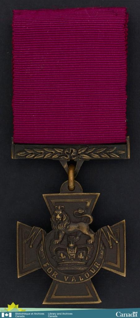 Photographie en couleur d'une médaille. Le ruban est cramoisi. La médaille cruciforme en bronze arbore un lion surplombant une couronne et une bannière, où l'on peut lire For Valour (pour bravoure).