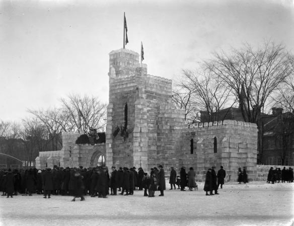 Photographie en noir et blanc illustrant des gens se tenant debout, possiblement à faire la file, autour du château de glace.