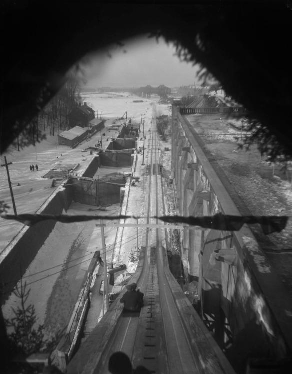 Photographie en noir et blanc illustrant le haut de la descente en toboggan en regardant vers le bas vers la rivière, à côté des écluses Rideau. Les traces sont très longues et creuses, et rejoignent presque le pont Alexandra au loin.