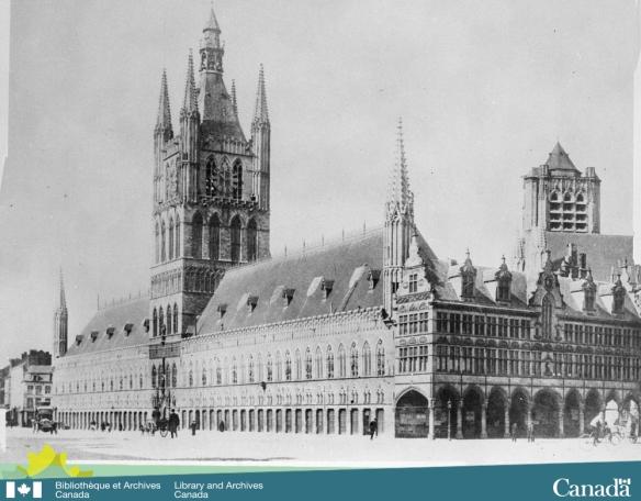 Photo noir et blanc d'un édifice gothique richement décoré et des édifices adjacents.