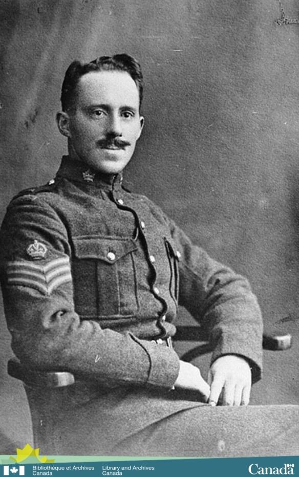 Photographie en noir et blanc d'un jeune soldat, en uniforme militaire, arborant une moustache et assis sur une chaise.