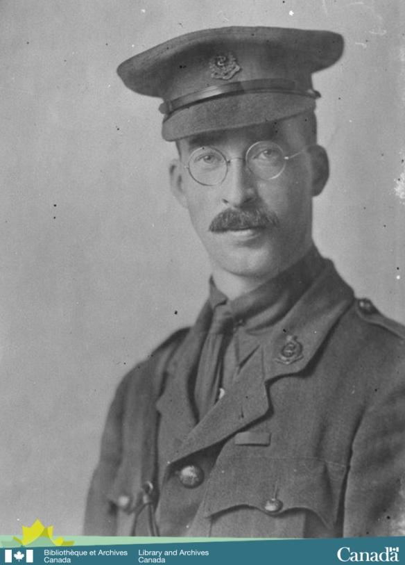 Photographie en noir et blanc montrant un jeune homme, en uniforme militaire, avec une moustache et des lunettes, regardant directement le photographe.