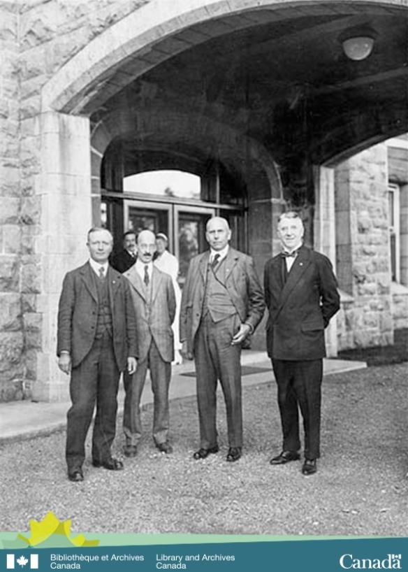 Photographie en noir et blanc montrant quatre hommes debout devant la porte d'un édifice. À l'arrière-plan, on voit une infirmière et un homme regardant la scène.