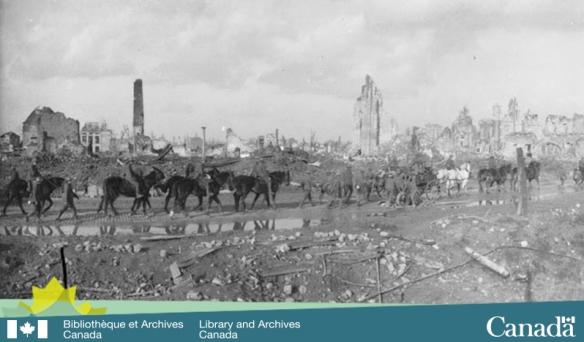 Photo noir et blanc d'une ville ravagée par la guerre. Une colonne de troupes composée majoritairement d'hommes à cheval traverse la ville.