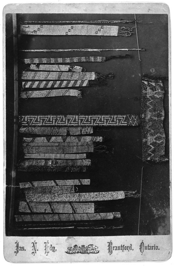 Photo noir et blanc montrant divers colliers et cordons de wampum.