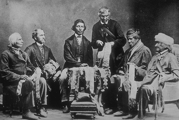 Photo noir et blanc montrant six hommes regardant des wampums. Cinq individus sont assis et le sixième semble expliquer un collier de wampum.