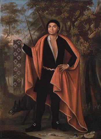 Peinture à l'huile sur toile montrant un homme debout dans une forêt avec un loup à ses pieds. Il est vêtu de noir et porte une écharpe rouge et tient dans sa main un collier de wampum.