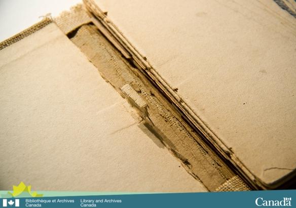 Photographie couleur montrant le dos détaché d'un carnet de croquis. La marque du ruban de couture est parfaitement visible sur la garde collée et la première page du feuillet.