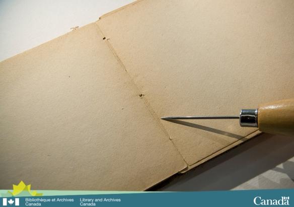 Photographie couleur montrant un carnet de croquis ouvert posé à plat sur une table. Une alène indique les marques du fil à coudre sur le papier.