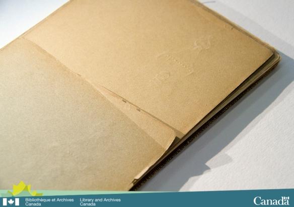 Photographie en couleur montant un carnet de croquis qui a des marques profondément enfoncées sur l'une des pages.
