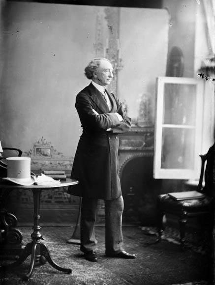 Images de sir John A. Macdonald, debout, portant un pardessus. Il adopte plusieurs poses dans un décor des studios Topley, tenant parfois un chapeau et une canne.